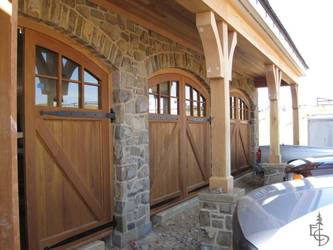 Arched carriage doors grace a beautiful stone carriage house.