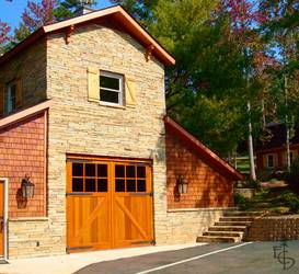 A beautiful stone barn with diagonal braced carriage barn doors.