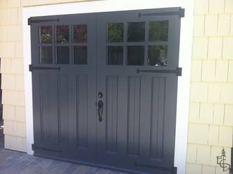 Beautifully painted Olympic style door on a shingle sided carriage house garage.